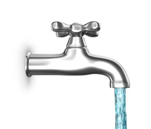 Water tap with flowing water isolated on white